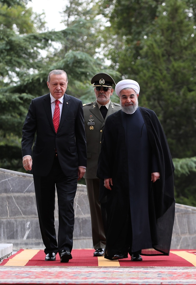 Iranian President Hassan Rohani walks next to Turkish President Recep Tayyip Erdogan during a welcome ceremony in Tehran, Wednesday. — AFP