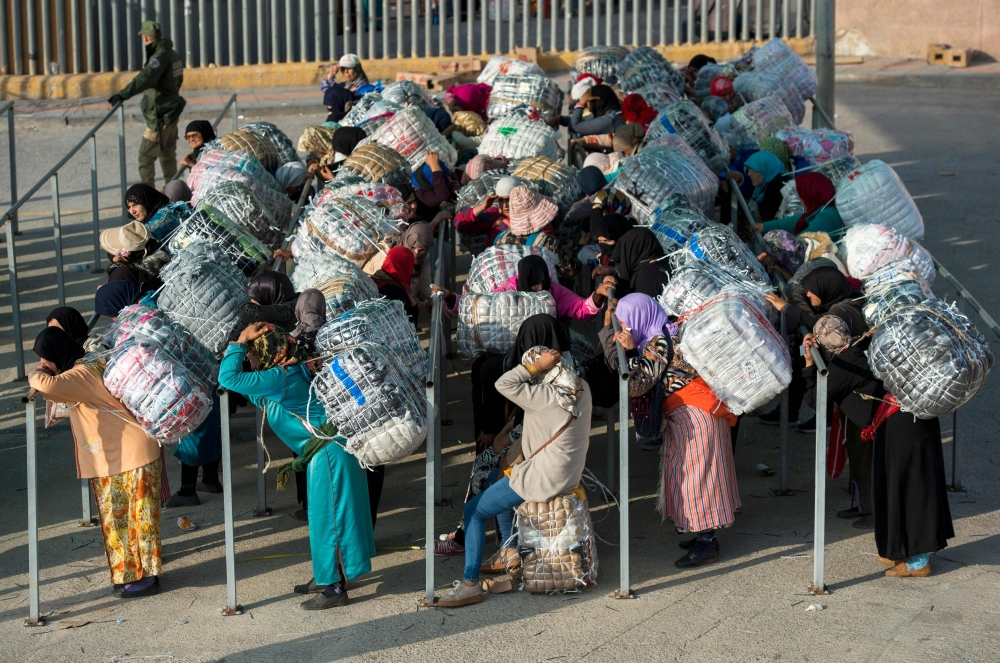 Female Moroccan porters carrying bundles of goods on their backs wait to pass through customs at the El-Tarajal border before crossing from Spain's North African enclave of Ceuta into Morocco. Along the border between Spain's North African enclave Ceuta and Morocco, thousands of women eke out a living lugging back-breaking loads of contraband in an illicit traffic tolerated by officials. — AFP