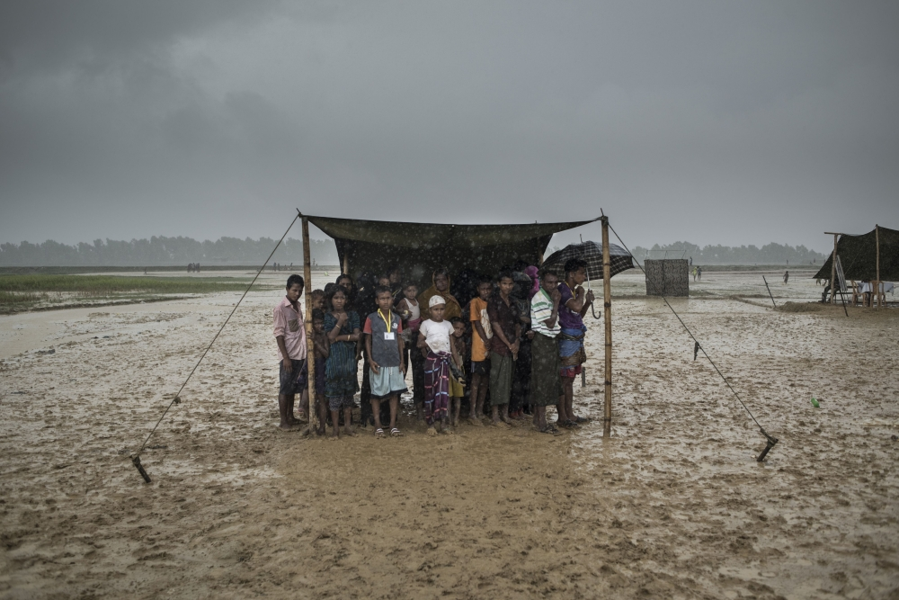 Rohingya Muslim refugees take shelter from the rain during a food distribution at Nayapara refugee camp in Bangladesh's Ukhia district on Friday. — AFP