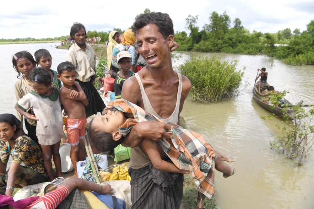 A Rohingya refugee reacts while holding his dead son after crossing the Naf river from Myanmar into Bangladesh in Whaikhyang on Monday. — AFP