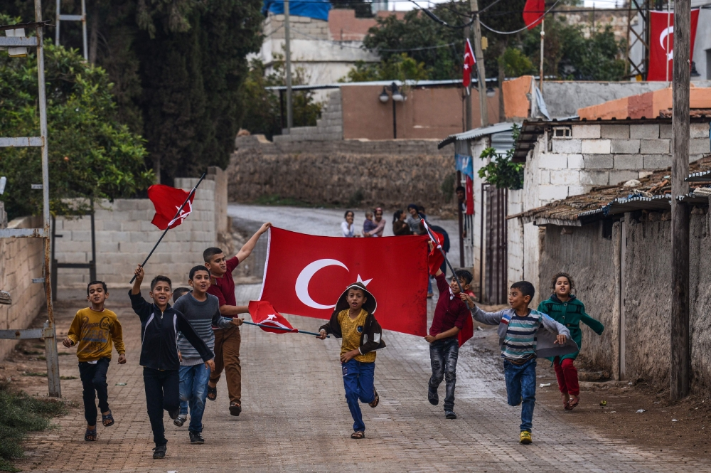 Turkish children run with Turkish national flags as they gesture towards Turkish army vehicles near the Turkey-Syria border in Reyhanli, Hatay province. — AFP