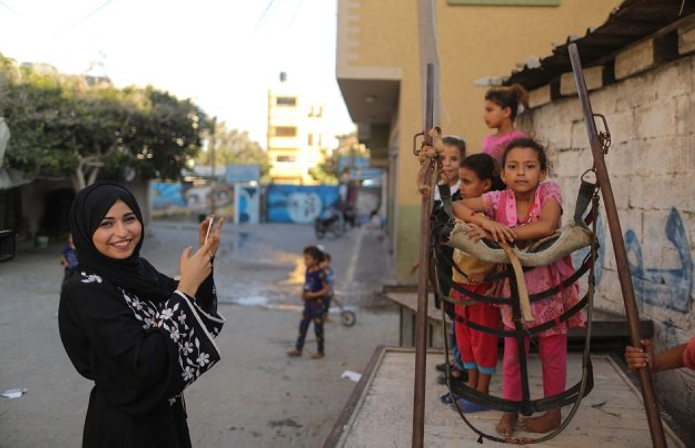 Abu Musabbeh, 21, uses her mobile phone to take pictures of children.