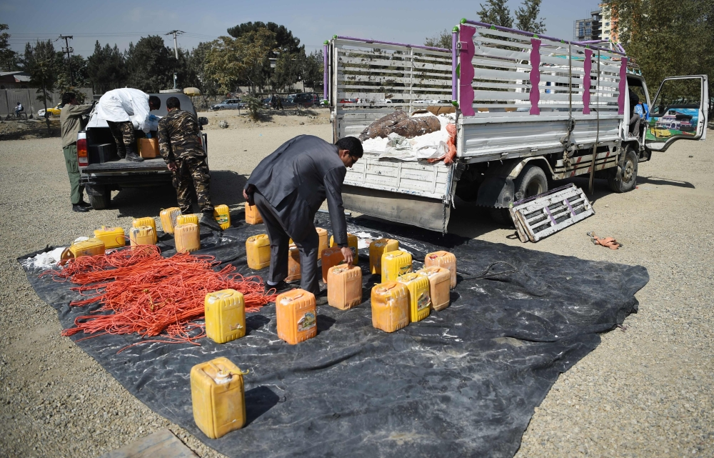 Afghan security force personnel load containers filled with explosive material on a vehicle after presenting it to the media at the National Directorate of Security (NDS) headquarters in Kabul on Sunday. — AFP