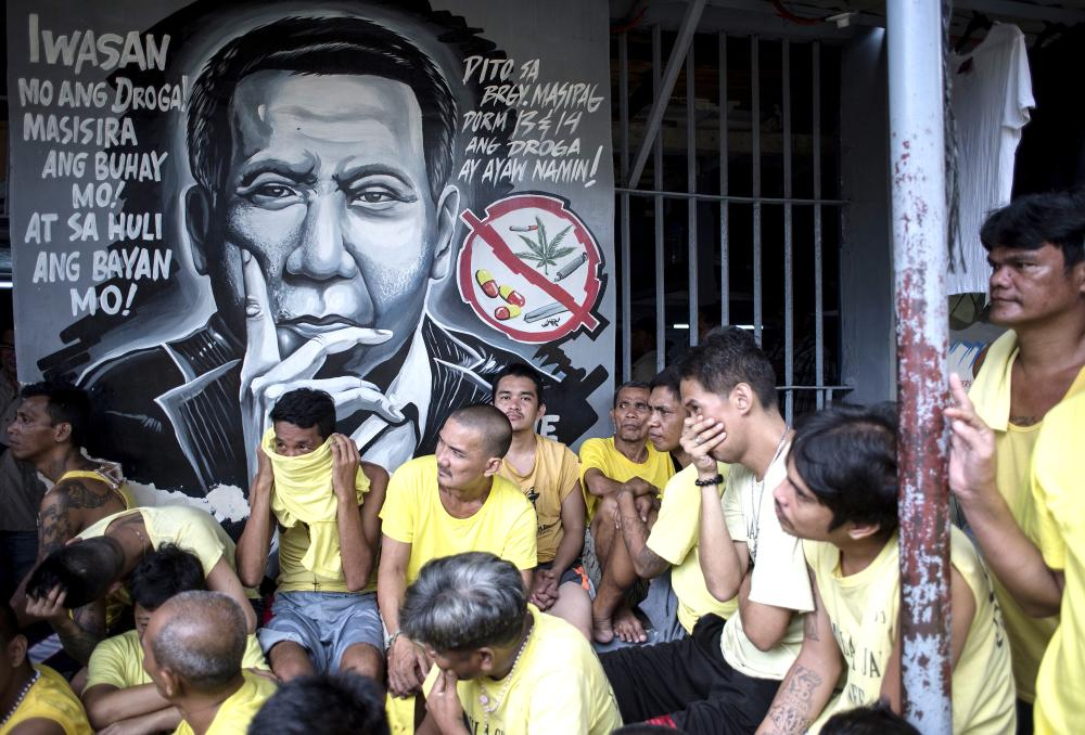 Inmates are seen beside a wall depicting Philippine President Rodrigo Duterte as authorities search for contraband at the Manila City Jail on Monday. — AFP