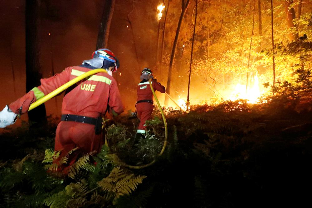 Firefighters from the Military Emergency Unit (UME) work to put out a forest fire near As Nieves, northern Spain, on Sunday. — Reuters