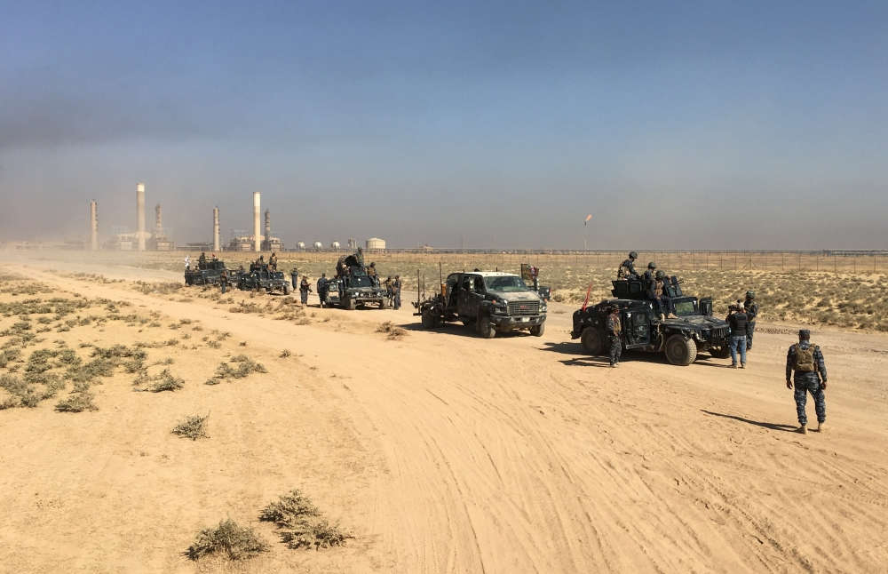 Members of Iraqi federal forces enter oil fields in Kirkuk on Monday. — Reuters