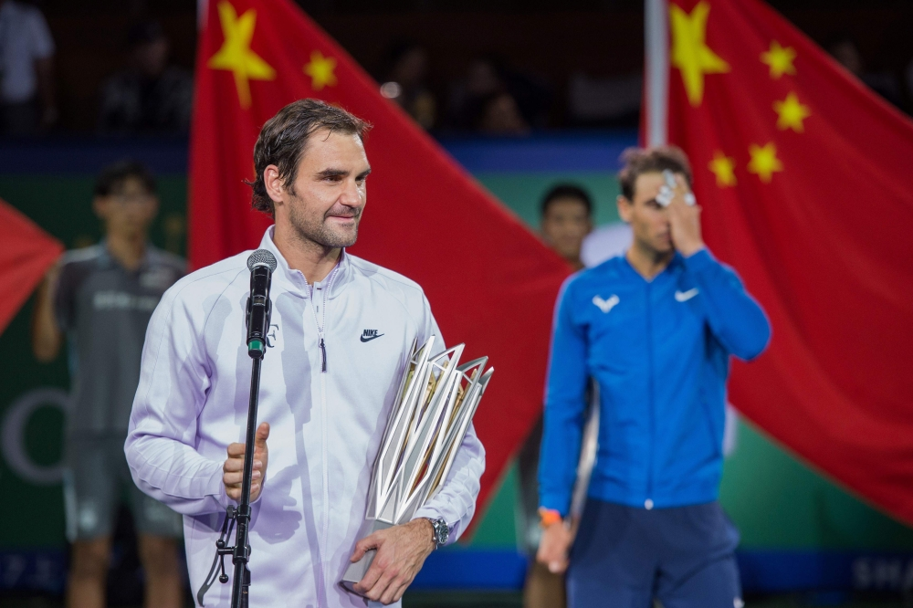 Winner Roger Federer of Switzerland (L) speaks in front of second-placed Rafael Nadal of Spain after the men's singles final match at the Shanghai Masters tennis tournament in Shanghai on Sunday. — AFP