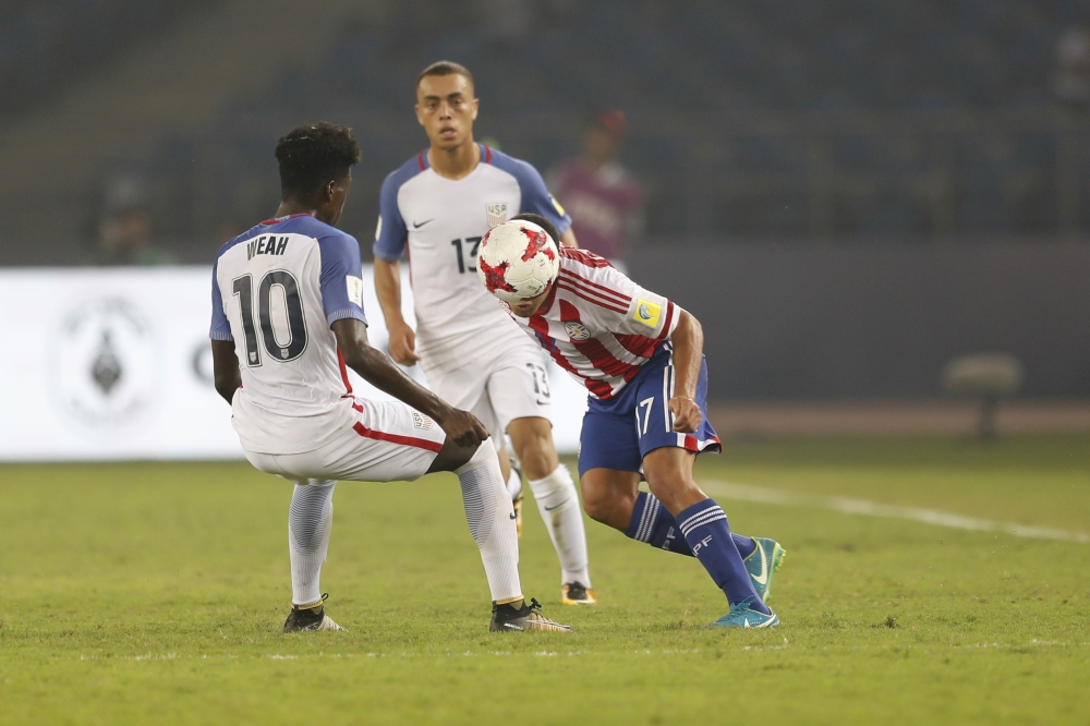 Paraguay's Fernando Cardozo heads the ball as US's Timm Weah tackles during their FIFA U-17 World Cup match in New Delhi, India, Monday. — AP