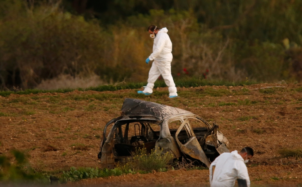Forensic experts walk in a field after a powerful bomb blew up a car (Foreground) and killed investigative journalist Daphne Caruana Galizia in Bidnija, Malta, on Monday. — Reuters