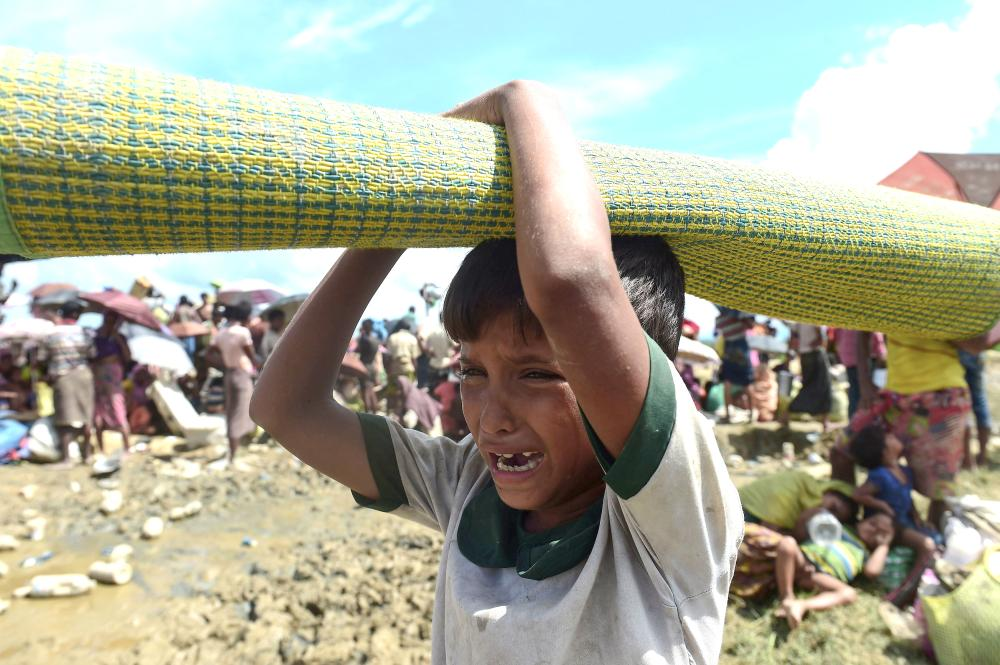 A young Rohingya refugee cries as he waits in an area near no man's land on the Bangladesh side of the border with Myanmar after crossing the Naf River, after being told by border guards they were not allowed to leave the area and reach the refugee camps near Ukhia, on Tuesday. — AFP