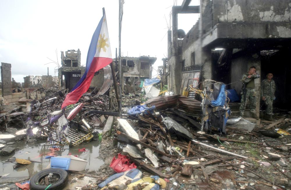 A Philippine flag is seen at destroyed houses in Bangolo town at Marawi city, southern Philippines, on Tuesday. — Reuters