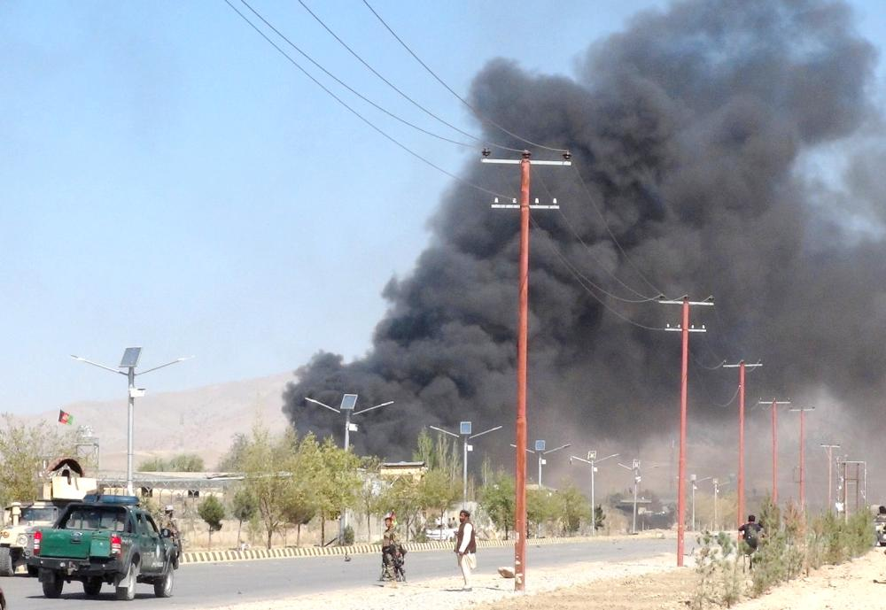 Smoke rises from police headquarters while Afghan security forces keep watch after a suicide car bomber and gunmen attacked the provincial police headquarters in Gardez, the capital of Paktia province, Afghanistan, on Tuesday. — Reuters