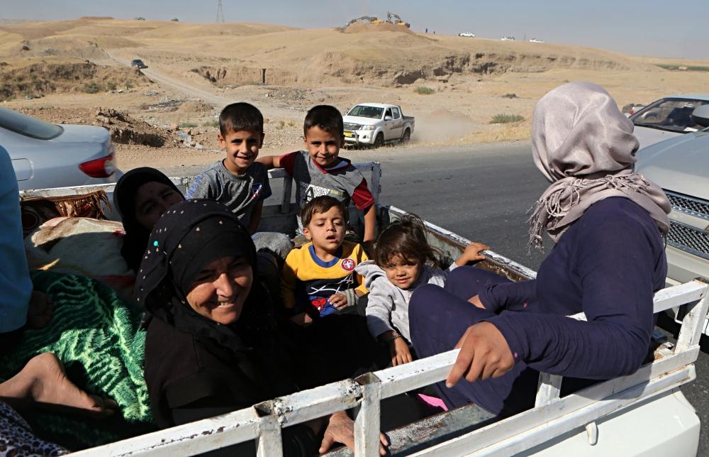 People return to Kirkuk, 290 kilometers (180 miles) north of Baghdad, Iraq, Tuesday. — AP
