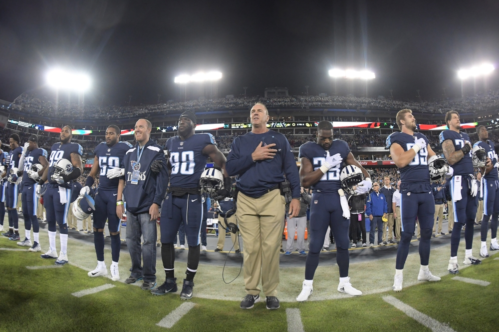 Tennessee Titans head coach Mike Mularkey stands with Titans players during the playing of the national anthem before an game against the Indianapolis Colts at Nissan Stadium. — Reuters
