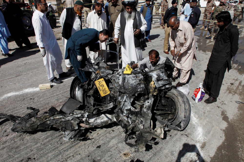 Security officials inspect a wreckage of a vehicle after a blast in Quetta, Pakistan, on Wednesday. — Reuters
