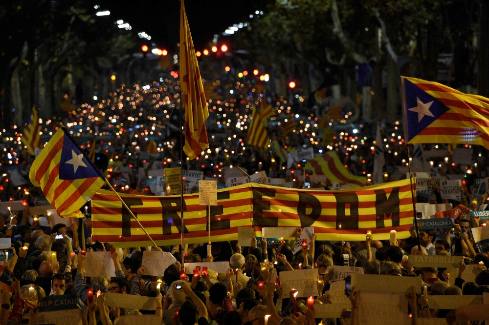 "People hold a giant Estelada (pro-independence Catalan flag) reading ""Freedom"" during candle-lit demonstration in Barcelona against the arrest of two Catalan separatist leaders on Tuesday. — AFP"