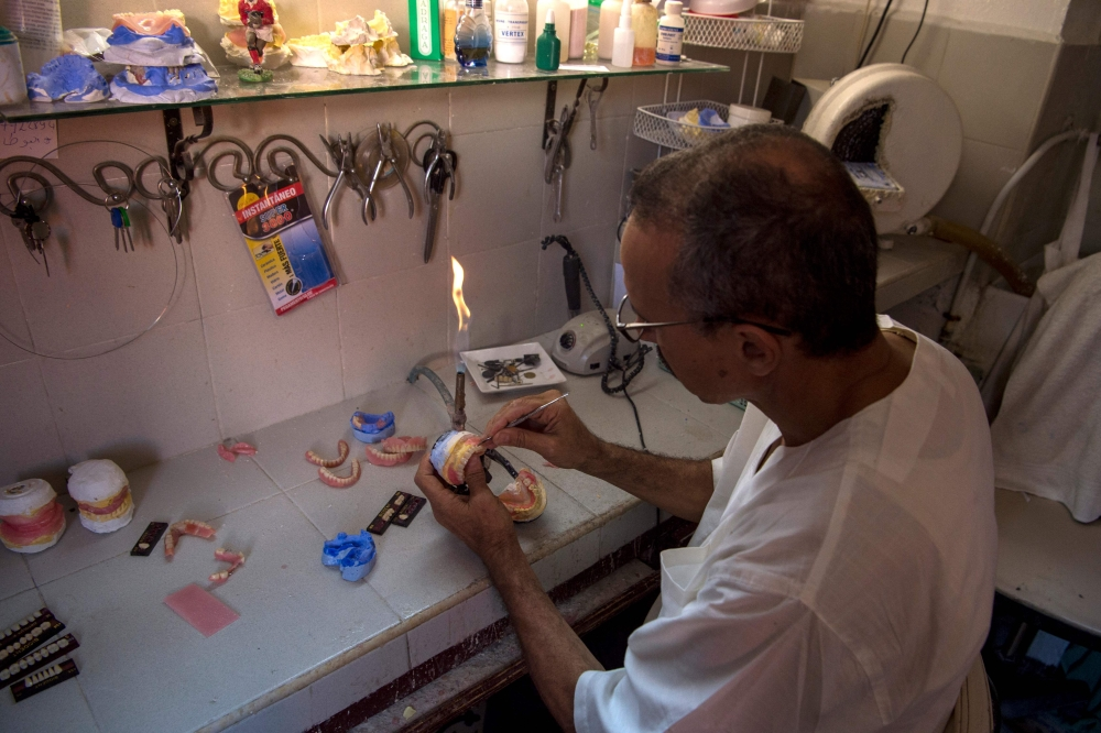 A dental technician works on dentures for a patient in the Moroccan capital Rabat. — AFP