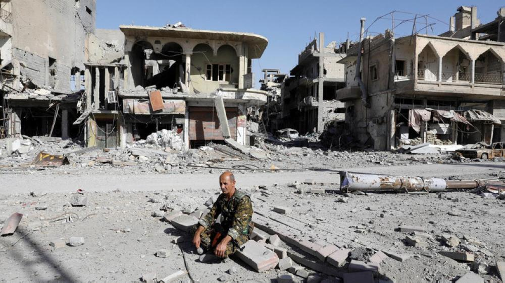 A fighter of Syrian Democratic Forces rests on rubble after Raqqa was liberated. — Reuters