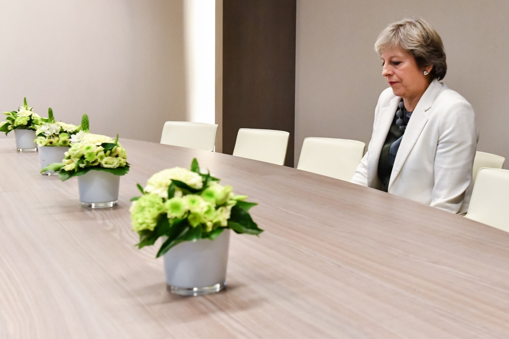 British Prime Minister Theresa May takes a seat as she arrives for a bilateral meeting with European Council President Donald Tusk during an EU summit in Brussels on Friday. The EU is expected to say that they will start internal preparatory work on a post-Brexit transition period and a future trade deal with Britain. — AFP