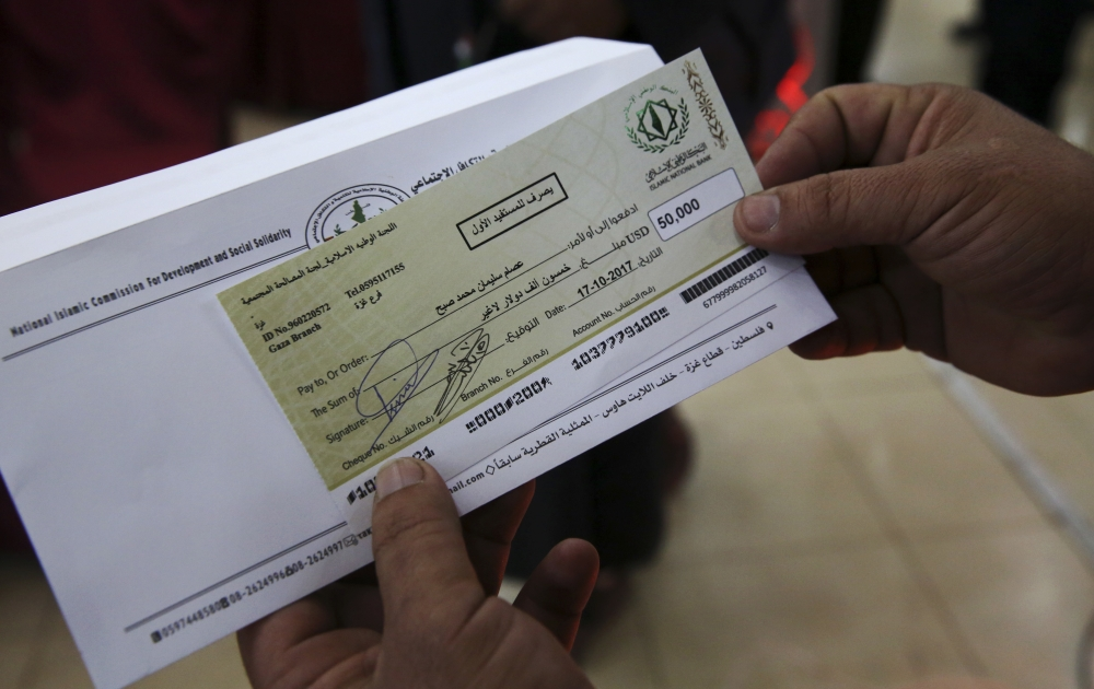 A relative shows a check for $50,000 to Esam Subeh's family during a social reconciliation ceremony in Beit Lahiya City, Gaza Strip. He was killed during Hamas and Fatah fighting in Gaza Strip in 2007. — AP