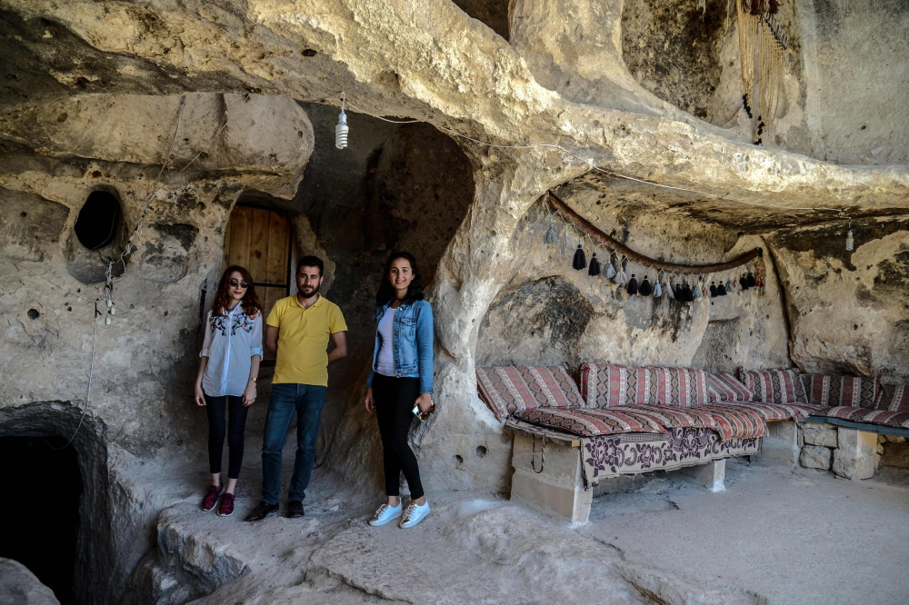 Tourists pose in historical caves in the Hasankeyf district in Batman.