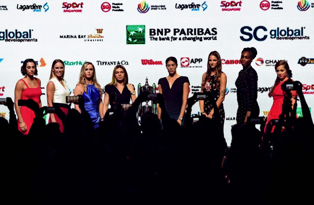 (From L) Caroline Garcia of France, Caroline Wozniacki of Denmark, Elina Svitolina of Ukraine, Simona Halep of Romania, Garbine Muguruza of Spain, Karolina Pliskova of Czech Republic, Venus Williams of the US and Jelena Ostapenko of Latvia pose during the draw ceremony of the WTA Finals in Singapore Friday. — AFP