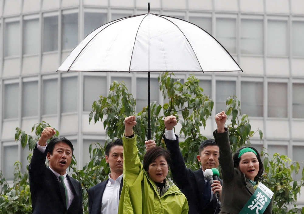 Head of Japan's Party of Hope and Tokyo Governor Yuriko Koike (C) and her party lawmakers raise their fists during the last day of campaigning for the October 22 lower house election, in Tokyo. — Reuters