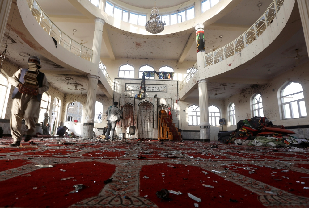 Afghan men inspect inside a mosque after Friday night's attack in Kabu. — Reuters
