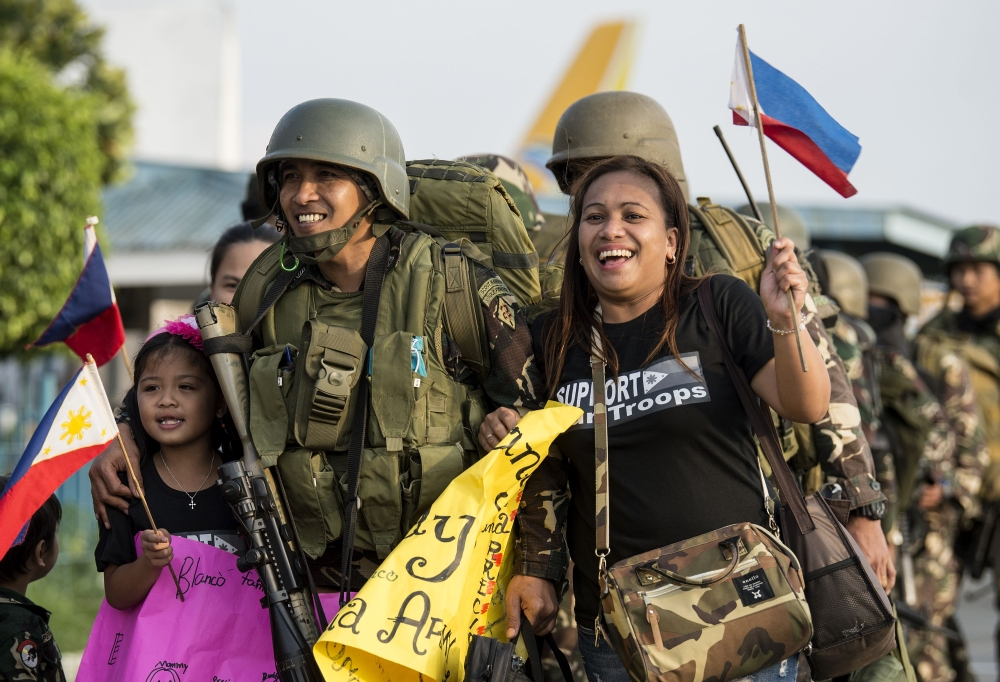 Philippine soldiers from Marawi are welcomed home by their relatives at Villamor Airbase in Manila. — AFP