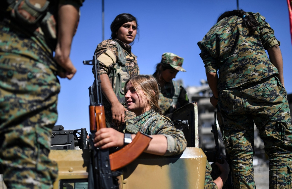 Kurdish female fighters of the Syrian Democratic Forces (SDF) gather during a celebration at the iconic Al-Naim square in Raqa after retaking the city from Daesh. — AFP