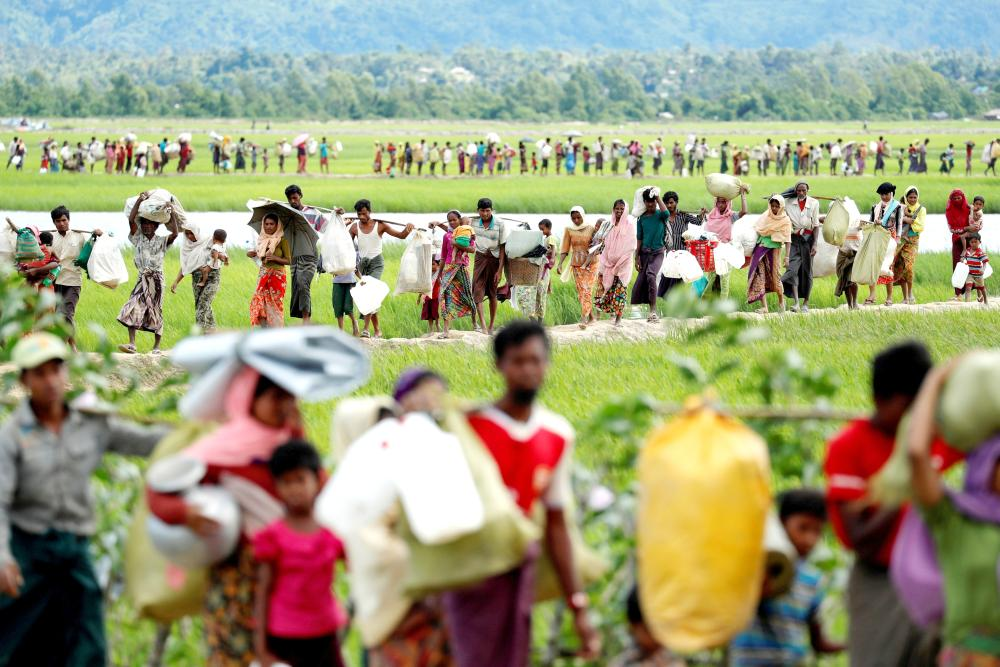 Photo shows Rohingya refugees, who crossed the border from Myanmar two days before, walk after they received permission from the Bangladeshi army to continue on to the refugee camps, in Palang Khali, near Cox's Bazar, Bangladesh. — Reuters