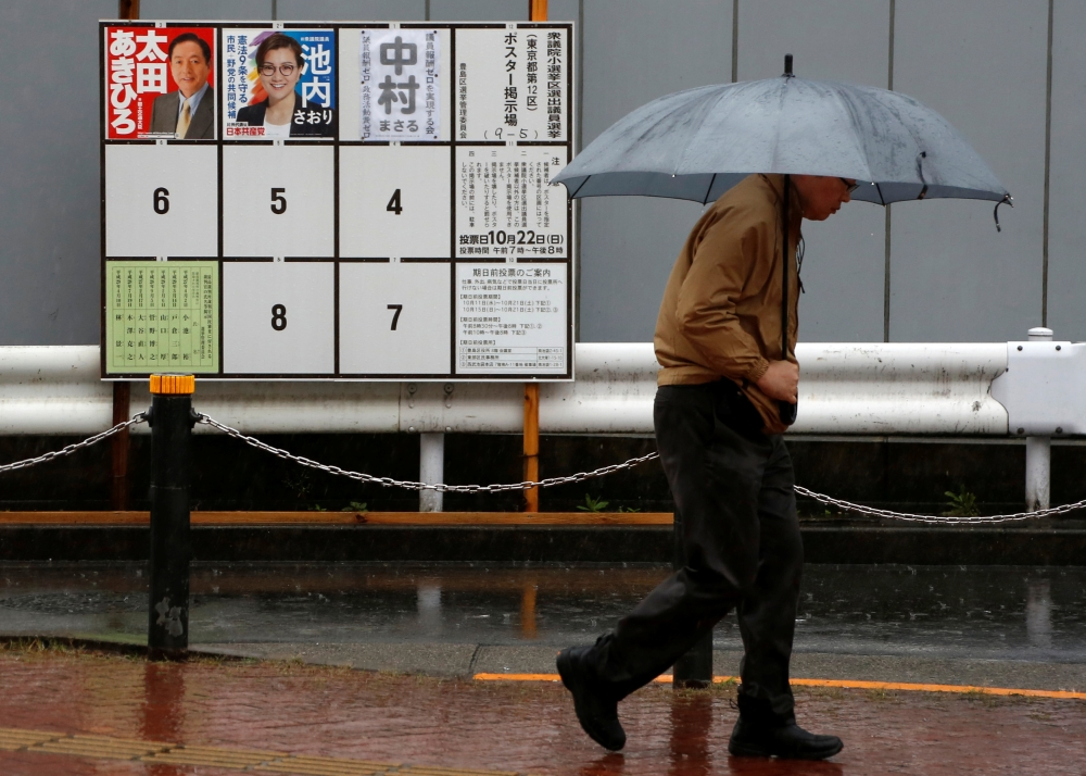 A man walks in the rain past election posters near a polling station as Typhoon Lan approaches Japan's mainland, in Tokyo, Japan, Sunday. — Reuters