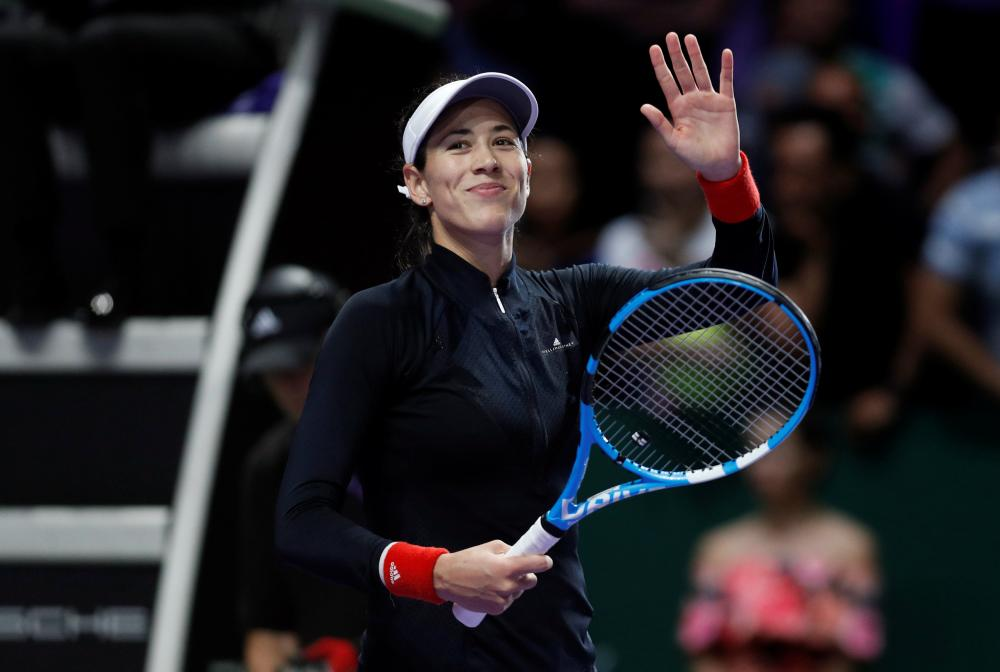 Spain's Garbine Muguruza celebrates winning her match against Latvia's Jelena Ostapenko at the WTA Tour Finals in Singapore Sunday. — Reuters