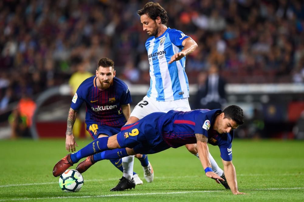 Barcelona's Lionel Messi (back) observes as Malaga's defender Paul Baysse challenges Barcelona's Luis Suarez (front) during their Spanish league football match at the Camp Nou Stadium in Barcelona Saturday. — AFP