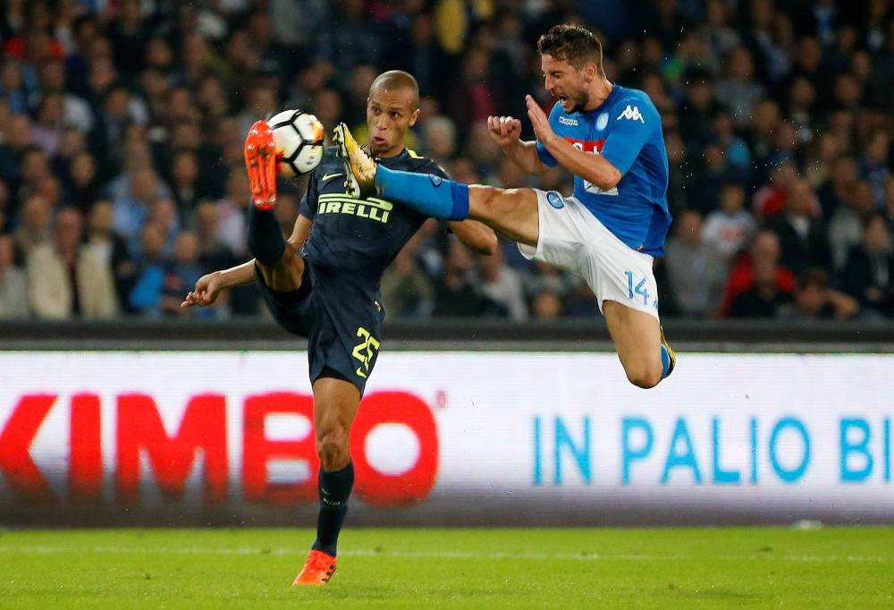 Napoli's Dries Mertens in action with Inter Milan's Miranda during their Intalian league football match at Stadio San Paolo in Naples Saturday. — Reuters