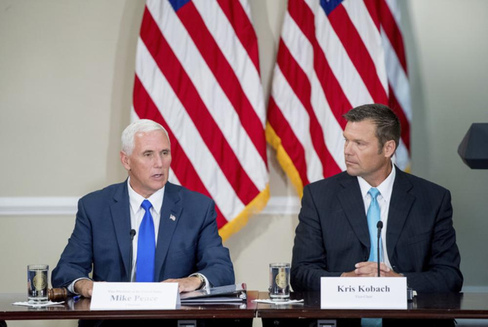 In this file photo, Vice President Mike Pence, left, accompanied by Vice-Chair Kansas Secretary of State Kris Kobach, right, speaks during the first meeting of the Presidential advisory commission on election integrity at the Eisenhower Executive Office Building. — AP