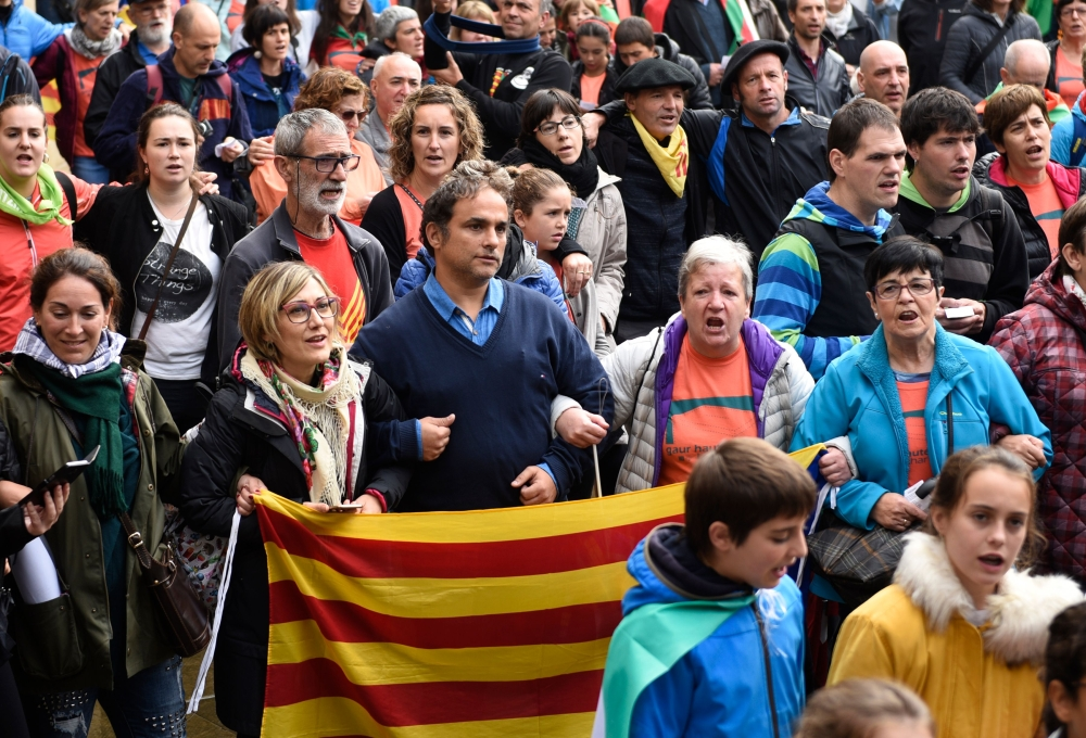 People hold Catalan pro-independence Estelada flags and Basque Country flags during a demonstration in the northern Spain Basque village of Beasain on Sunday during a protest action organized by