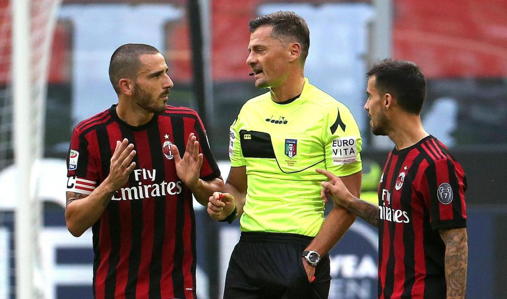 AC Milan defender Leonardo Bonucci (L) speaks with referee Piero Giacomelli (C) after receiving a red card during a Serie A soccer match against Genoa at the Giuseppe Meazza Stadium in Milan Sunday. — AP