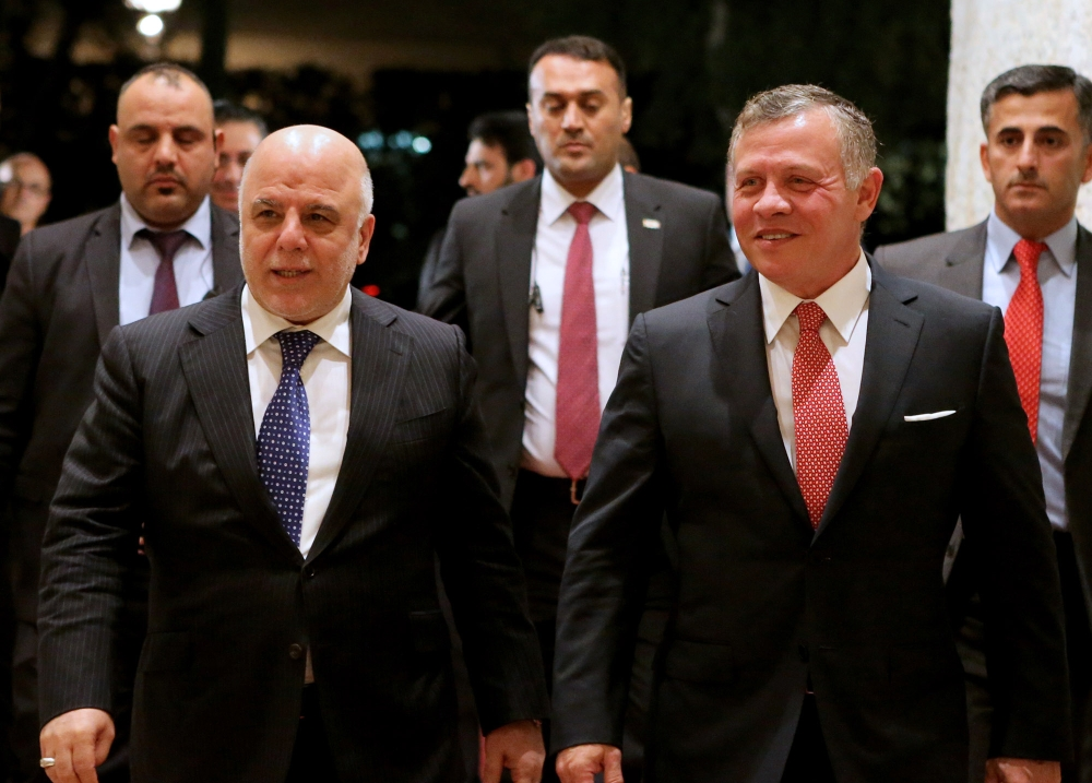 A handout picture released by the Jordanian Royal Palace on Sunday shows Jordan's King Abdullah II (R) and Iraqi Prime Minister Haider Al-Abadi heading for a meeting in Amman. — AFP