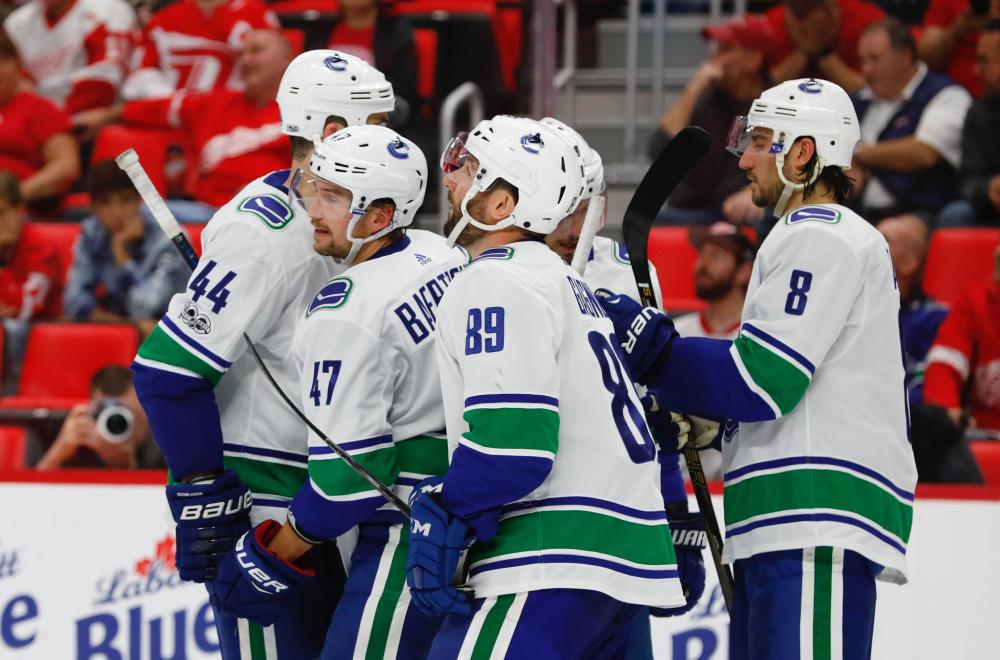 Vancouver Canucks' left wing Sven Baertschi (2nd L) is congratulated by teammates after scoring against Detroit Red wings during their NHL game in Caesars Arena in Detroit Sunday. — Reuters
