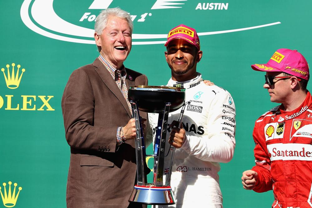 Winner Lewis Hamilton of Mercedes with former US president Bill Clinton and third place finisher Kimi Raikkonen of Ferrari on the podium during the US Formula One Grand Prix at Circuit of The Americas in Austin Sunday. — AFP