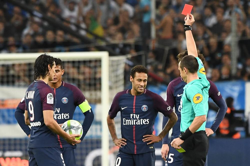 French referee Ruddy Buquet (R) shows a red card to Paris Saint-Germain's Neymar (C) during the French L1 football match against Marseille at the Velodrome Stadium in Marseille Sunday. — AFP
