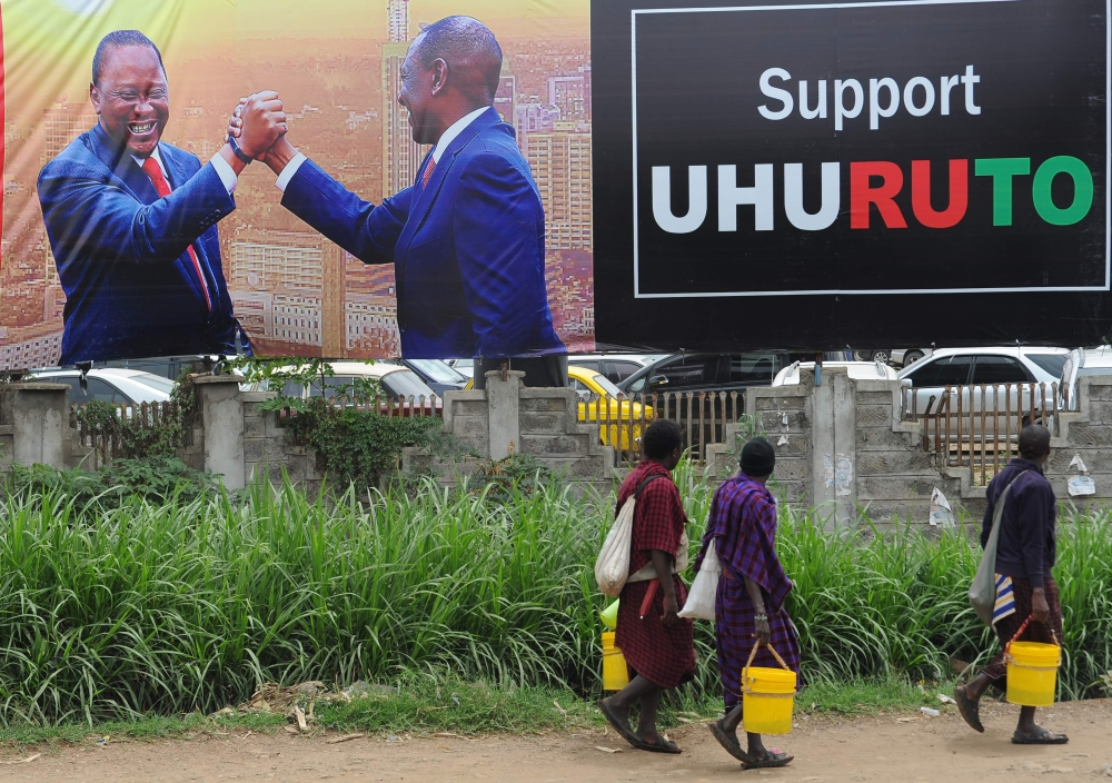 Pedestrians walk past the campaign poster of Kenya's President Uhuru Kenyatta and Deputy-President William Ruto in Nairobi on Monday, ahead of the repeat elections. — AFP