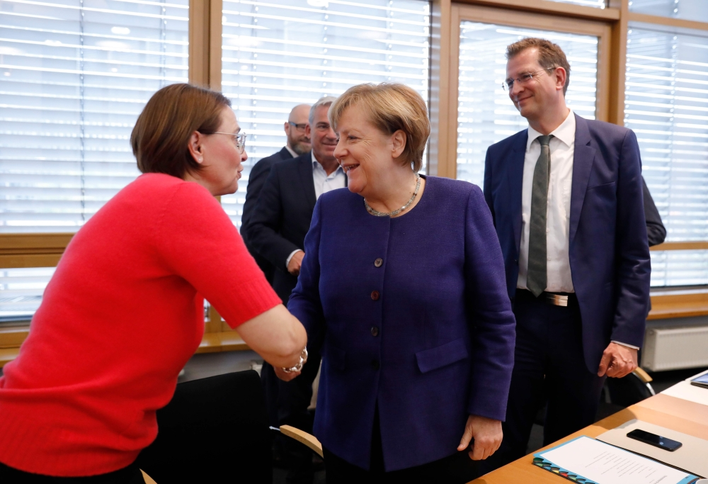 German Chancellor Angela Merkel (C) greets staff upon arrival for a meeting of the federal executive board of the Christian Democratic Union (CDU) in Berlin, on Monday on the eve of further exploratory talks between potential coalition partners. — AFP