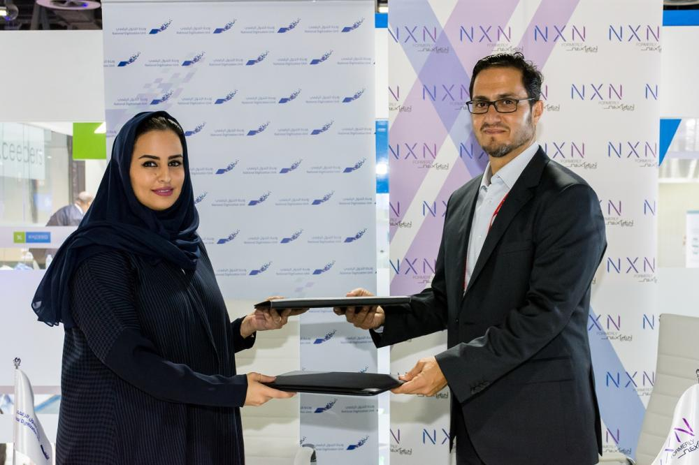 Mrs. Deemah Al-Yahya, Acting Chief Executive Officer of the National Digitization Unit; and Ghazi Atallah, CEO of NXN, exchange copy of the MOU after signing the deal
