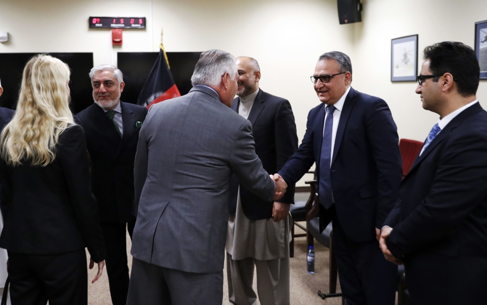 US Secretary of State Rex Tillerson greets Afghan Chief of Staff Salam Rahimi (2R) before meeting with Afghan President Ashraf Ghani at Bagram Air Field in Afghanistan on Monday. Tillerson paid a surprise visit to Afghanistan to discuss Washington's new strategy with Ghani, the US Embassy said. — AFP