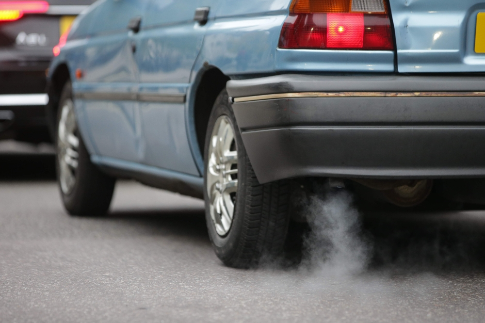 A car emits fumes from its exhaust as it waits in traffic in central London, England on Monday.  Drivers of the most polluting vehicles will face an extra daily charge for driving into central London on weekdays from Monday in a bid to improve air quality in one of Europe's most polluted cities. — AFP
