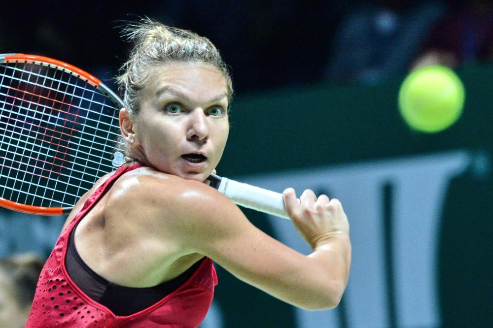 Simona Halep of Romania hits a return against Caroline Garcia of France during the WTA Finals Tennis Tournament in Singapore Monday. — AFP