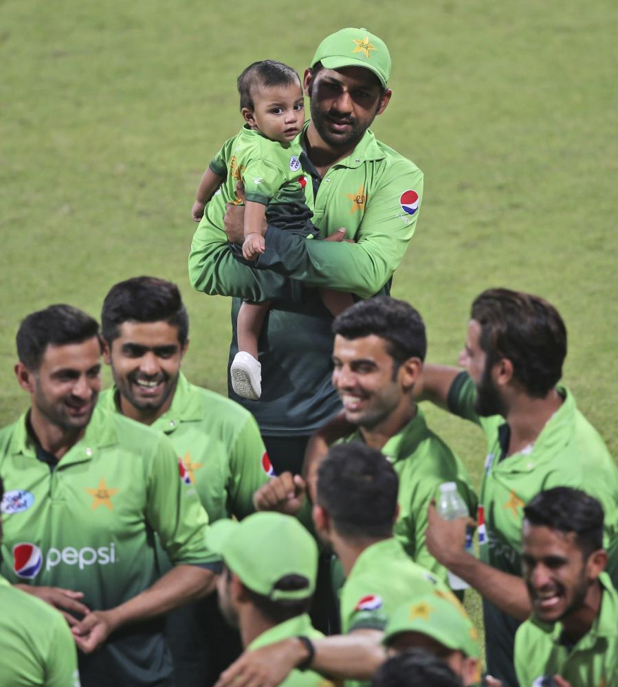 Pakistan's Sarfaraz Ahmed holds his child along with teammates after defeating Sri Lanka in Sharjah Monday. — AP