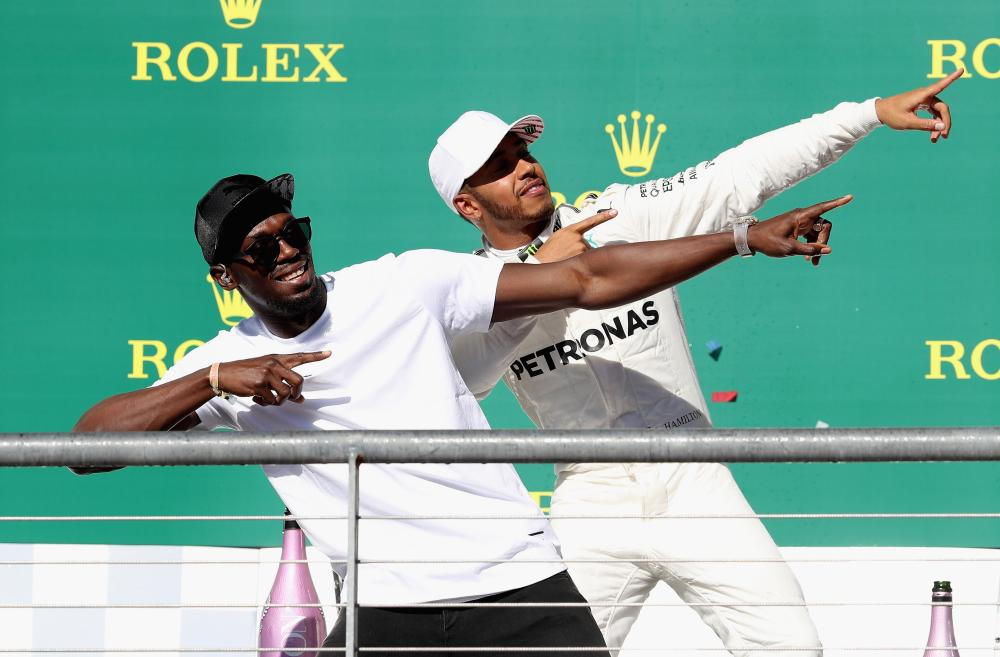 Race winner Lewis Hamilton of Great Britain celebrates on the podium with sprinting legend Usain Bolt during the US Formula One Grand Prix at Circuit of The Americas in Austin Sunday. — AFP
